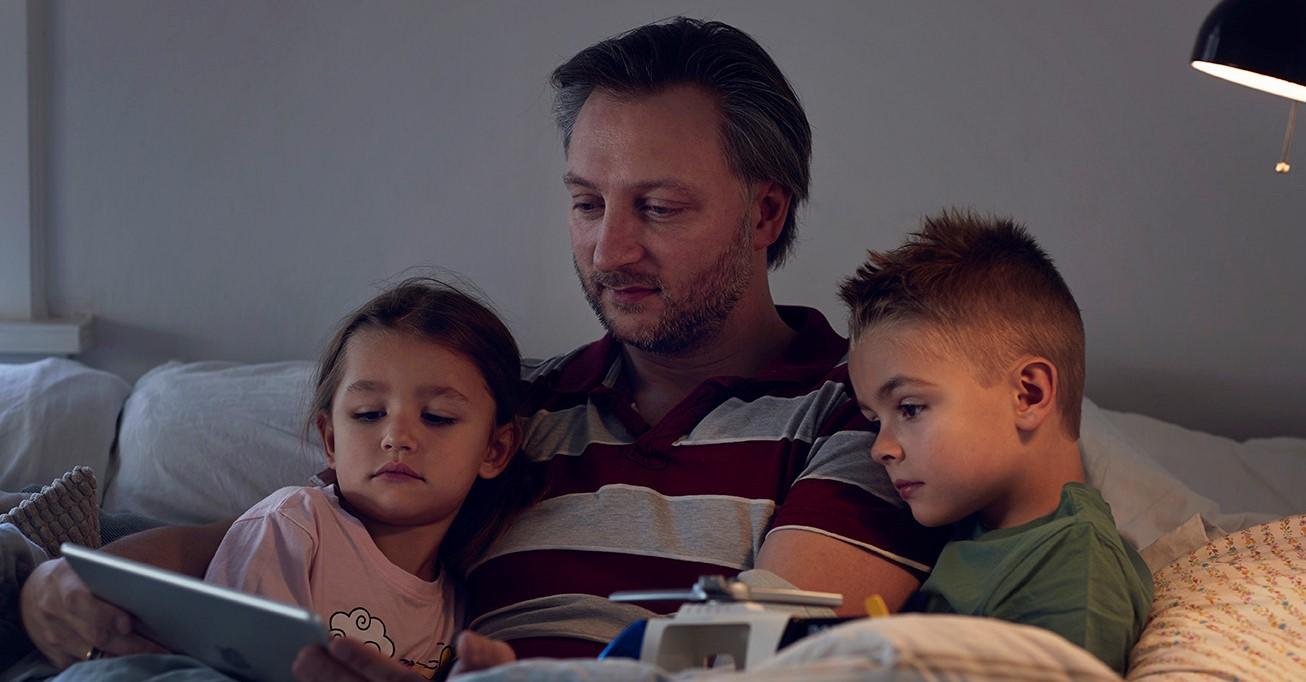 Far med to børn læser højt fra eReolen i sofaen