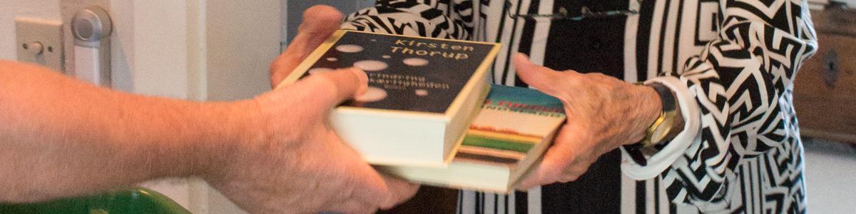 Person giver en anden person bøger