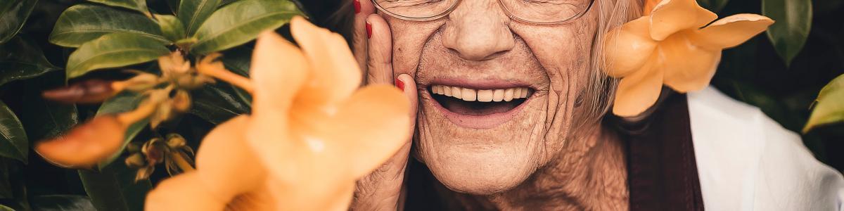 kvinde smiler i blomsterbusk