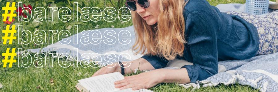Kvinde læser liggende på et tæppe