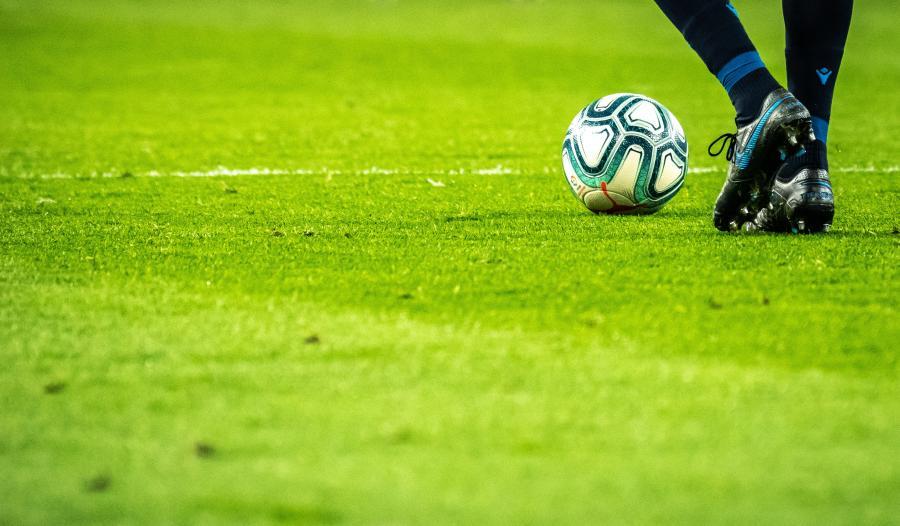 fodboldstøvler og fodbold på grøn græsplæne