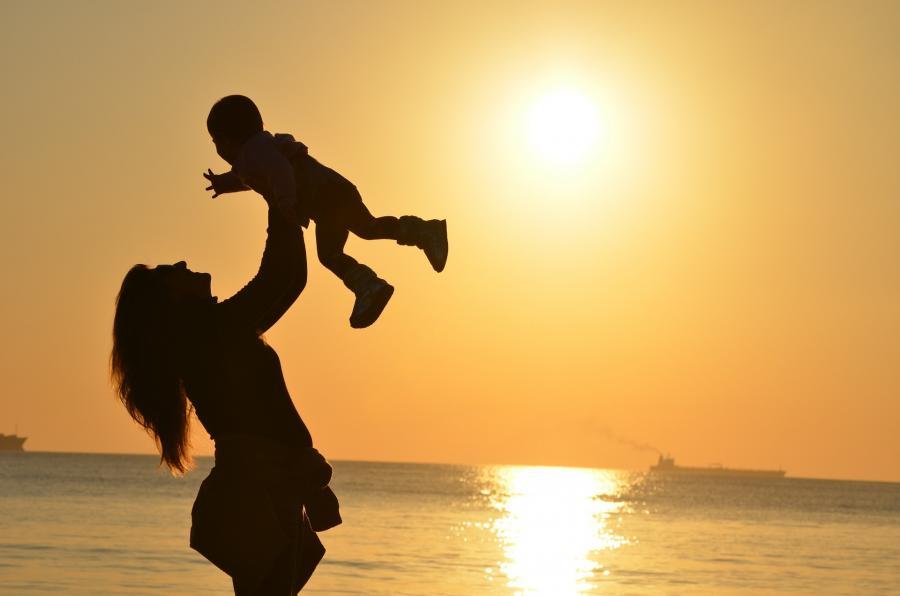 Mor svinger sit barn i solnedgang