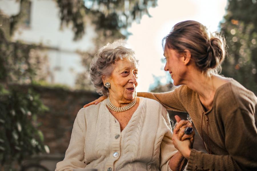 Ældre kvinde og midaldrende kvinde holder hinandens hænder og ser kærligt på hinanden