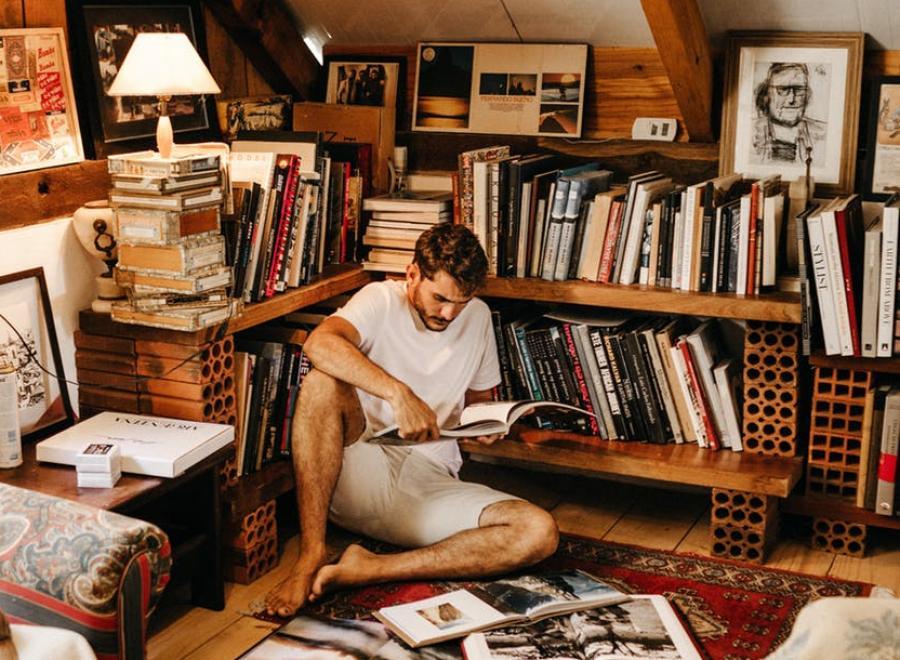 Mand der sidder op ad en bogreol og læser