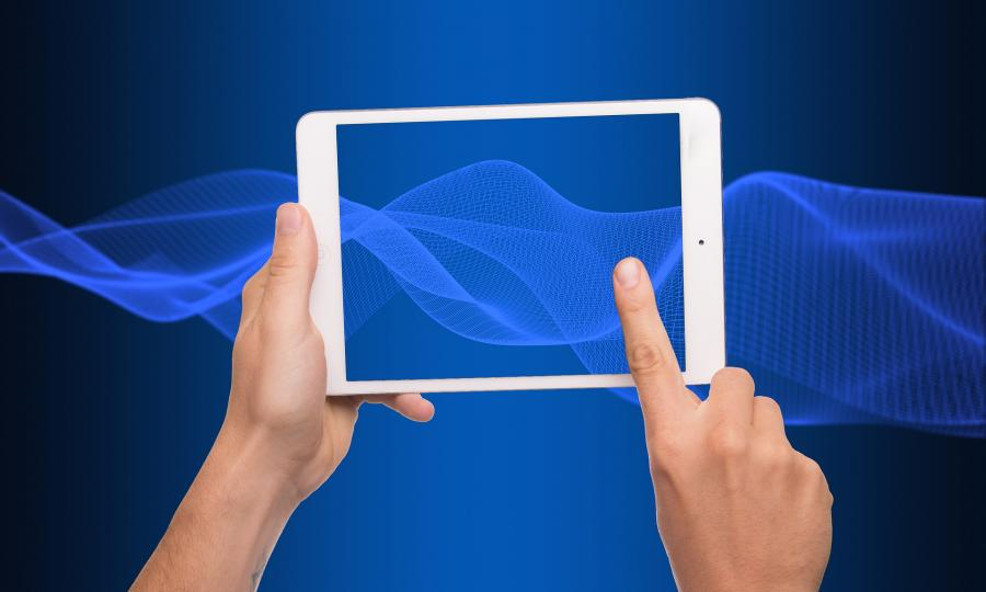 En hånd holder en tablet og peger med en finger på skærmen, blå baggrund
