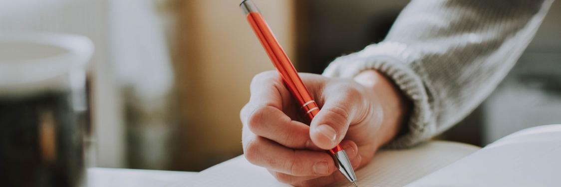 Mandehånd skriver i en notesbog med orange kuglepen